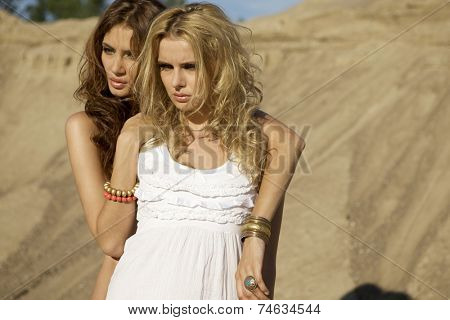 Two beautiful sensuality attractive and pretty girls friends - blond and brunette woman over sand background in white fashionable elegance dress