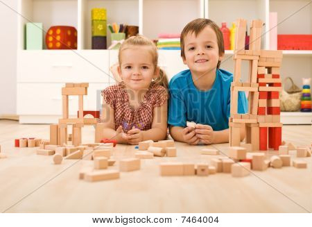 Happy Kids With Wooden Blocks On The Floor