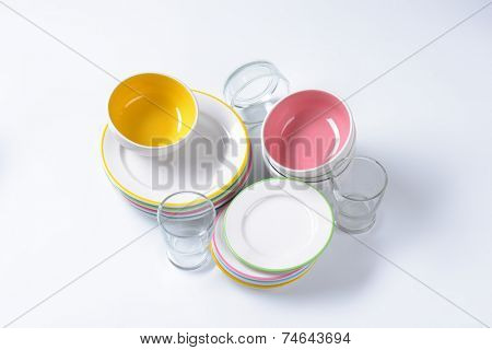 colorful dinnerware set includes bowls, plates and glass