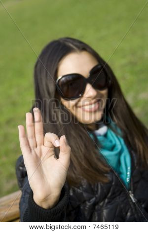 Beautiful girl in a park smiling. Hand sign OK