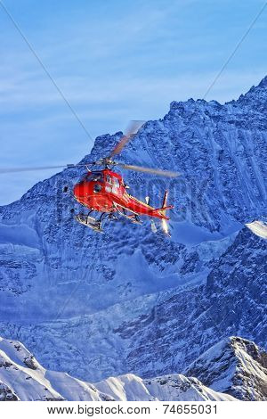 Red Helicopter In Swiss Alps In Winter Sunshine