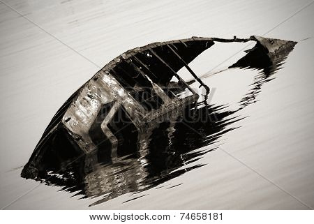 rusty sunken boat in ripples water