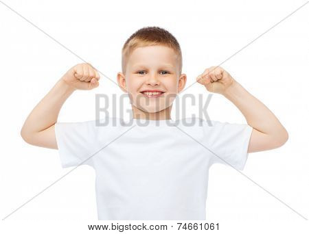 t-shirt design, strength, health, sport and fitness concept - little boy in blank white t-shirt showing muscles