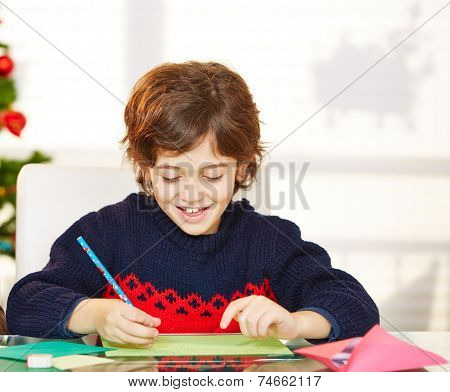Happy boy writing his wishlist for christmas eve