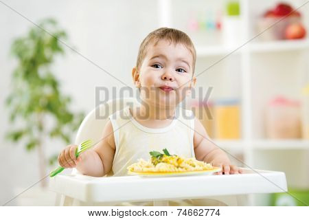 toddler boy in a highchair for feeding with a fork and a plate i