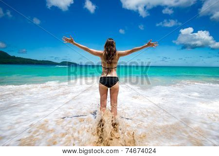 Young girl in bikini with raised arms greeting tropical sea and sun on beach - freedom vacation
