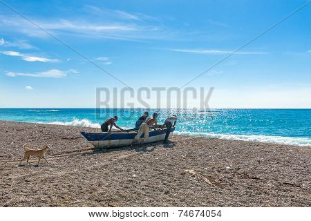 Four unidentified local fishermen pushing their boat to the sea and preparing for fishing dog follow
