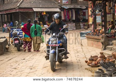 BHAKTAPUR, NEPAL - DEC 7, 2013: Unidentified Nepalese people in street of Bhaktapur. More 100 cultural groups have created an image Bhaktapur as Capital of Nepal Arts.