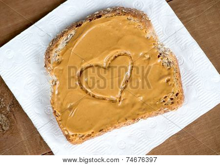 Tosted Peanut Butter Sandwich On Tissue Against Wooden Board With Heart Shape