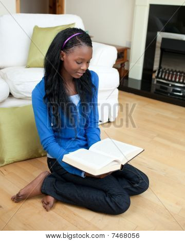 Concentrated Woman Reading A Book Sitting On The Floor