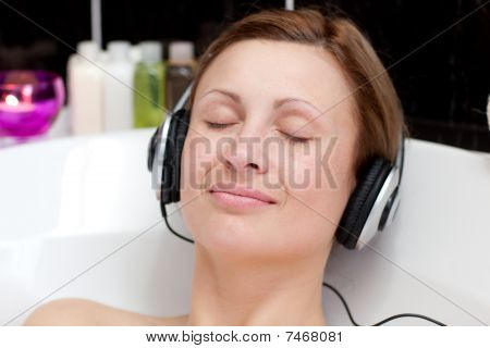 Close-up Of A Relaxed Young Woman Listening Music In A Bubble Bath