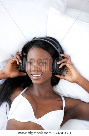 Radiant Woman Listening Music Lying On Her Bed