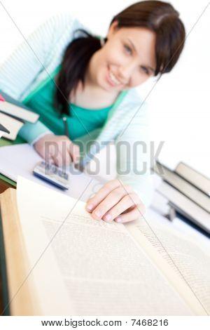 Positive Student Doing Her Homework On A Desk