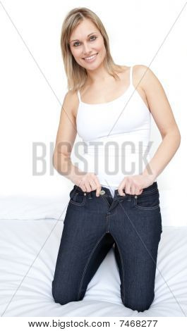 Smiling Woman Putting On Tight Jeans On A Bed