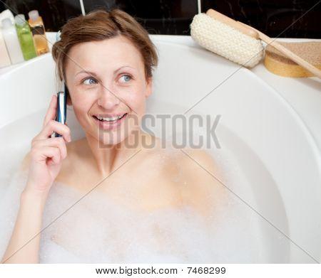 Radiant Woman Talking On Phone In A Bubble Bath