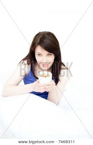 Sorriso atraente mulher tomando um café sentado em sua cama