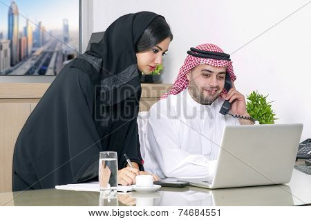Business Meeting in office , arabian businessman & arabian Secretary wearing hijab working on laptop