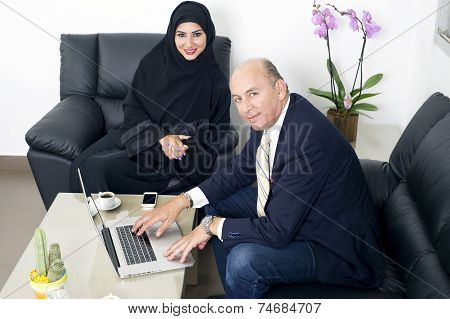 Multiracial Business meeting between a Senior Businessman & a woman wearing Hijab