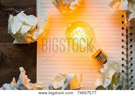Note book and light bulb on wood table