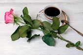 stock photo of beside  - Red rose lying on the table beside a cup of coffee - JPG
