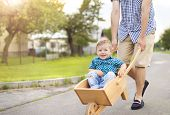 picture of wheelbarrow  - Young father pushing his little son in wooden wheelbarrow on road on sunny day - JPG