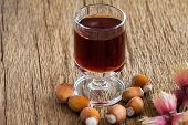 stock photo of hazelnut  - Homemade Hazelnut liqueur in a glass and hazelnuts of an old rustic wooden table - JPG