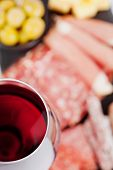 image of charcuterie  - Glass of red wine with charcuterie assortment on the background - JPG