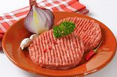 stock photo of beef-burger  - raw minced beef burger with fresh onion and garlic - JPG