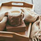pic of knitting  - Cup of hot tea with lemon dressed in knitted warm winter scarf on brown wooden tabletop - JPG
