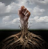 stock photo of addict  - Addiction freedom and breaking out concept as a human hand in a fist escaping from tree roots that were holding it down as a symbol for human rights and fighting for individual independence and liberation - JPG