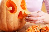 stock photo of hollow  - Hollowing out pumpkin to prepare halloween lantern - JPG
