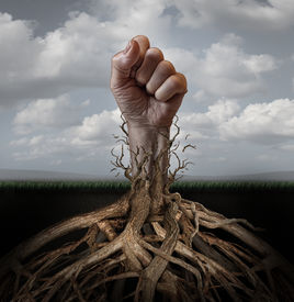 image of freedom speech  - Addiction freedom and breaking out concept as a human hand in a fist escaping from tree roots that were holding it down as a symbol for human rights and fighting for individual independence and liberation - JPG