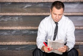 foto of unemployed people  - Young unemployed man is looking for a job in the newspaper sitting on the stairs - JPG