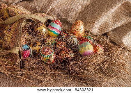 Colorful Painted Easter Egg From Fabric Bag On Hay