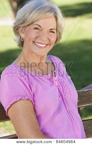 Portrait of an attractive elegant senior woman sitting outside with green grass behind her.