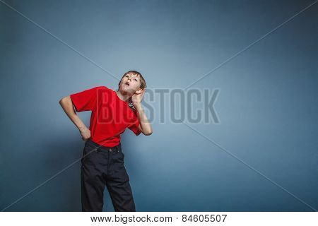 Boy, teenager, twelve years a in  red shirt holding his ear hand
