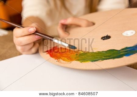Woman Holding Paintbrush And Choosing Paint On Pallet