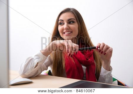 Portrait of a smiling woman with stylus looking away