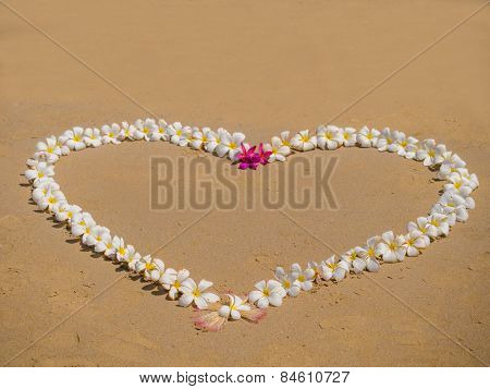 Heart made of flowers on the  beach love concept.