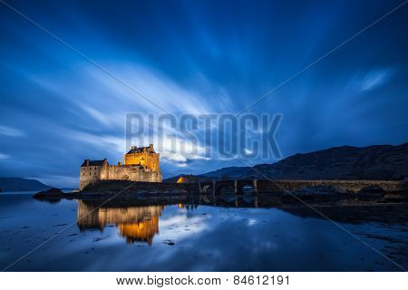 A castle lit up at night near the Isle of Skye