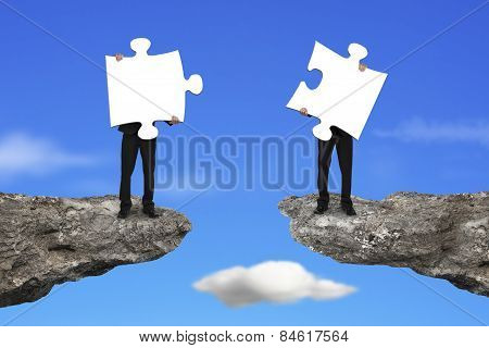 Businessmen Holding Jigsaw Puzzles To Connect On Cliff With Sky