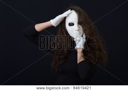 white theatrical mask in her hands.on a dark background