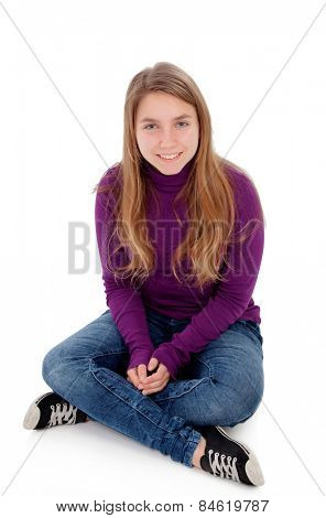 Adorable blonde teenager looking at camera sitting on floor isolated on a white background