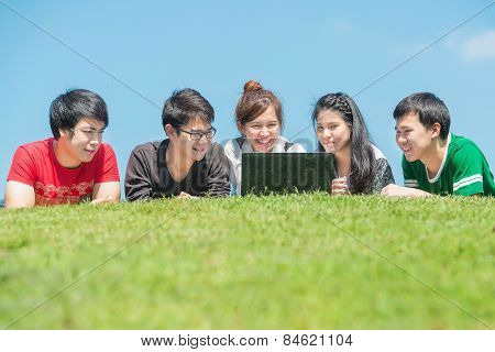 Group Of Young Student Using Laptop Together In The Park
