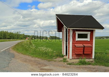 Landscape Of Red Wooden Bus Stop Shelter With Two Mail Boxes