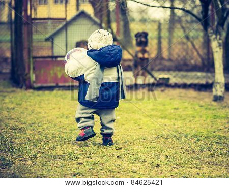 Child Walking With Ball