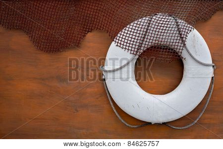 White life belt with fishing nets on wooden wall