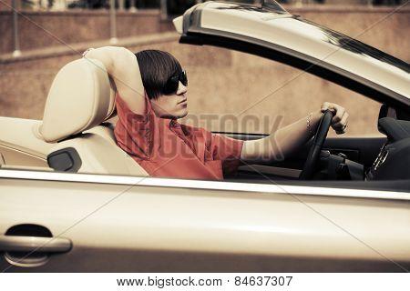 Young man driving a convertible car