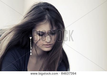 Sad young woman with long hairs looking down
