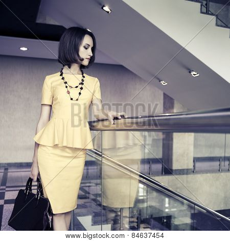 Young fashion business woman with handbag in office interior
